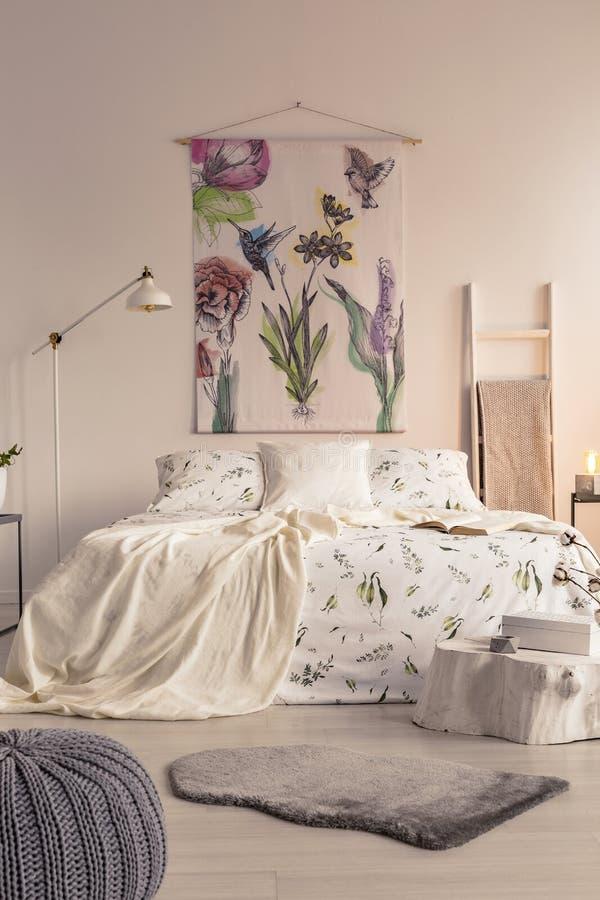Vertikal sikt av en pastellfärgad sovruminre med en stor säng i mitt och en målad tygkonst på väggen arkivbild