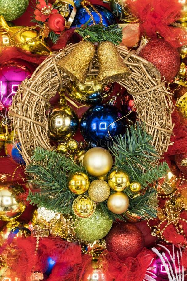 Vertikal sikt av julkransen med färgrika struntsaker i bakgrunden royaltyfri foto