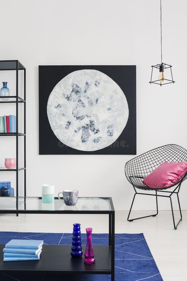 Vertikal sikt av månediagrammet på väggen av den moderiktiga fåtöljen för stilfull vit th för vardagsrum inre, verkligt foto arkivfoto