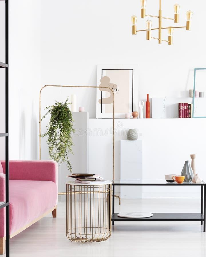 Vertikal sikt av vardagsrum i konstsamlares lägenhet med guld- detaljer arkivbild
