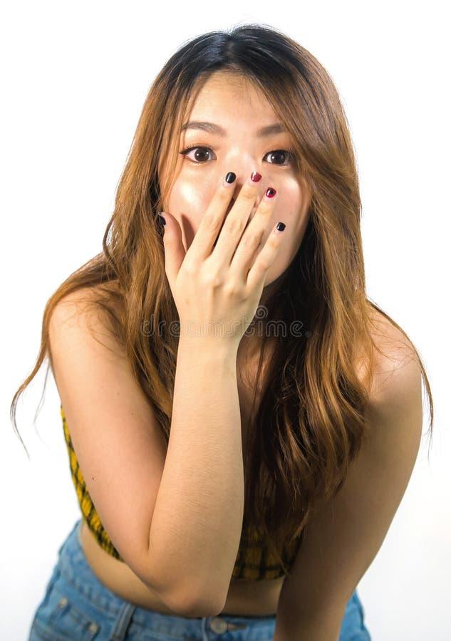 Vertikal stående av den unga chockade och förvånade härliga asiatiska koreanska kvinnan som täcker munnen med handen i misstro oc royaltyfria foton