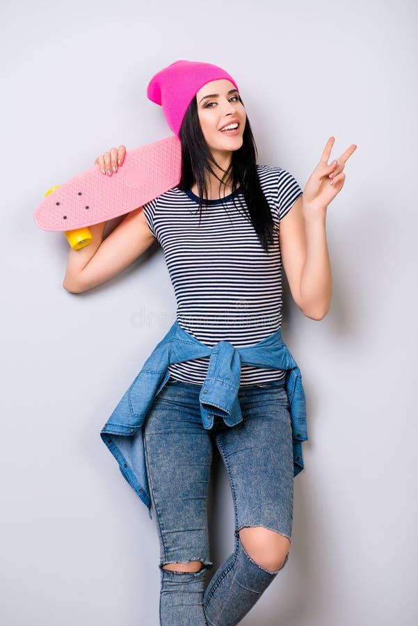 Vertikal stående av den unga le kvinnan med skateboarden på henne royaltyfria foton