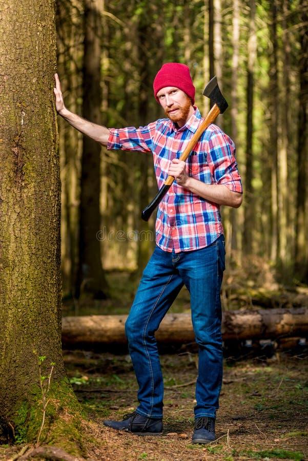 Vertikal stående av en hellång skäggig skogsarbetare med en yxa arkivbilder