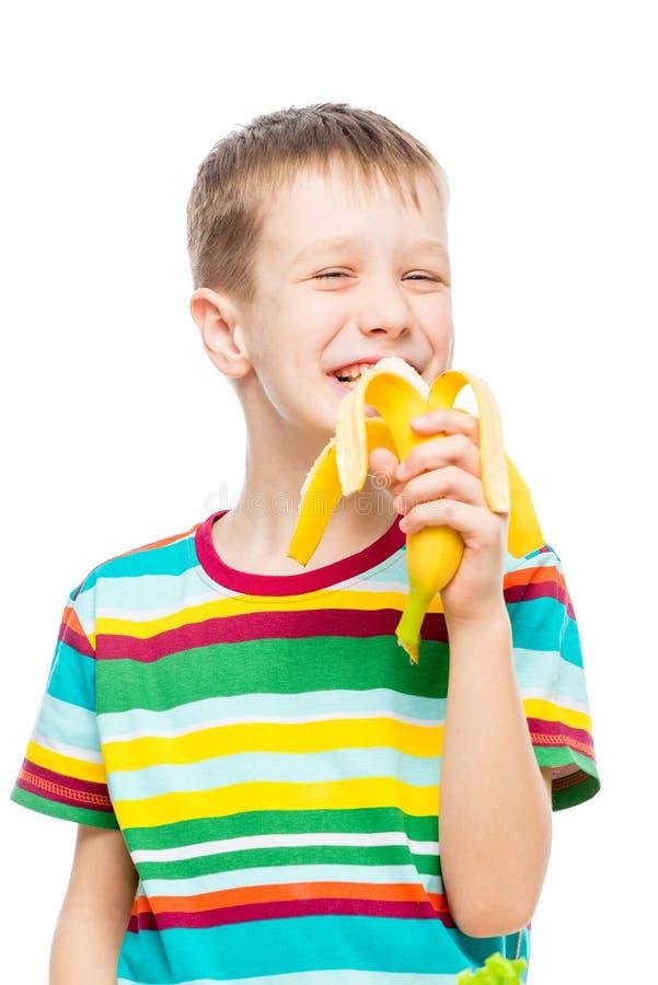 vertikal stående av en pojke som äter en smaklig banan på en vit bakgrund arkivfoton