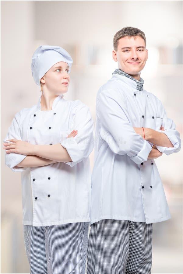 vertikal stående av ett lyckat lag av yrkesmässiga kockar i dräkter mot bakgrunden arkivbild