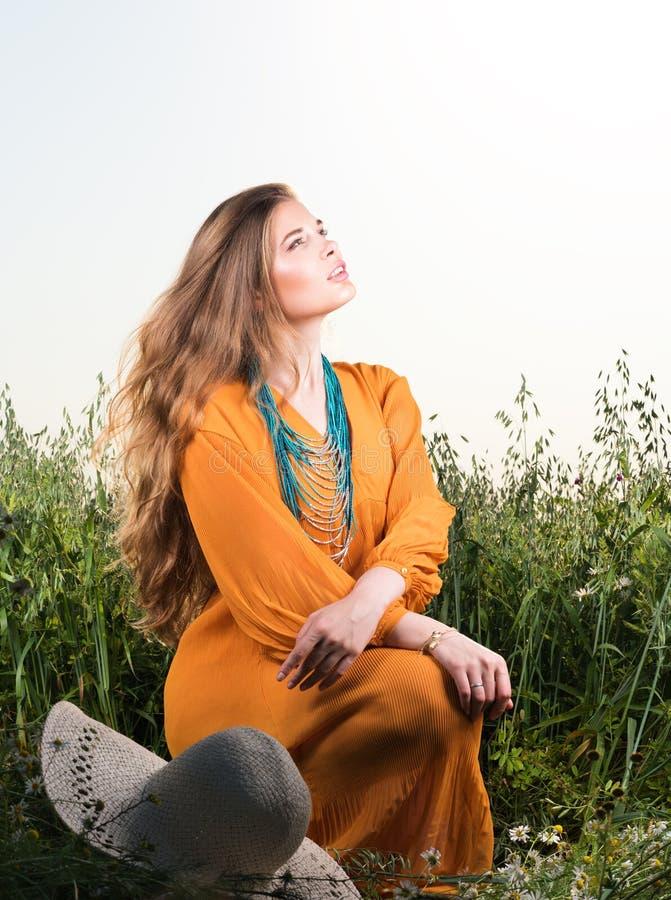 Vertikal stående av ett sammanträde för ung kvinna i fält som ser upp royaltyfria foton