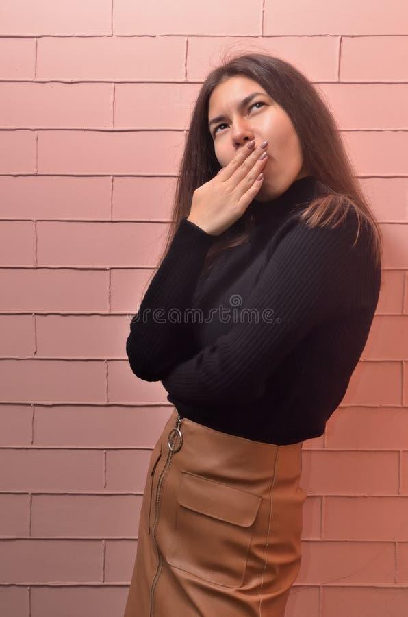 Vertikal stående för närbild av en härlig flicka i ett svart omslag och en brun kjol som misse arkivfoto