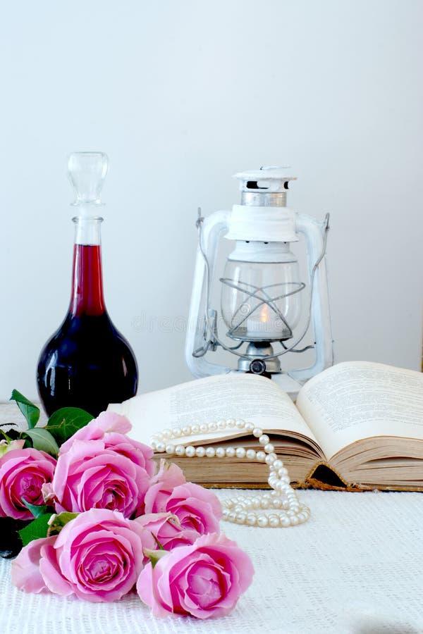 Vertikal stilleben på en vit bakgrund med en bok, en gammal lykta och en flaska av vin, en begåvad bukett av rosa rosor och ärta arkivfoto
