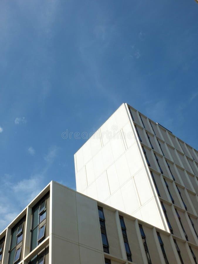 Vertikal vinkelsidosikt av en vit hög vit konkret byggnad med solljus och blå solig himmel reflekterade i fönstren royaltyfria foton