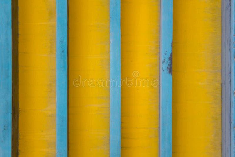 Vertikala blålinjen på en smutsig gul bakgrund med skuggor Textur för grov yttersida arkivbild
