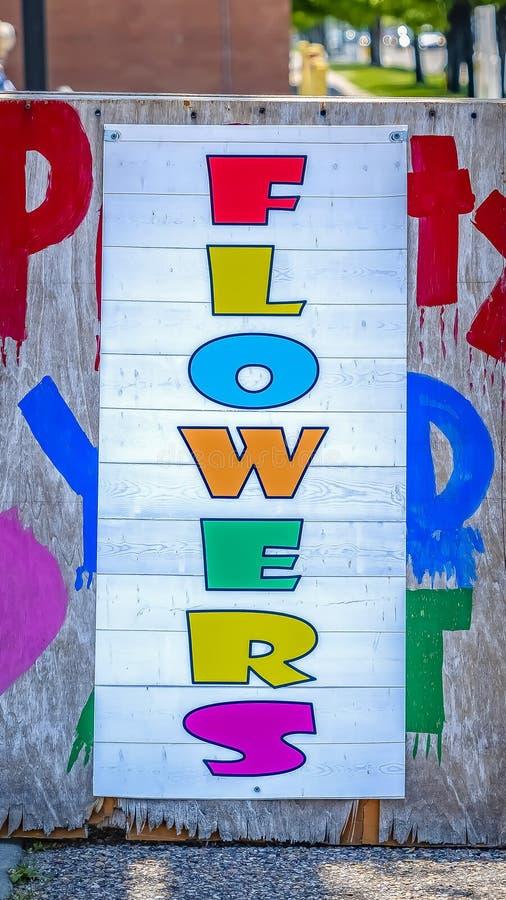 Vertikala blommor undertecknar med en färgrik stilsort som fästas till ett ridit ut träbräde royaltyfri bild