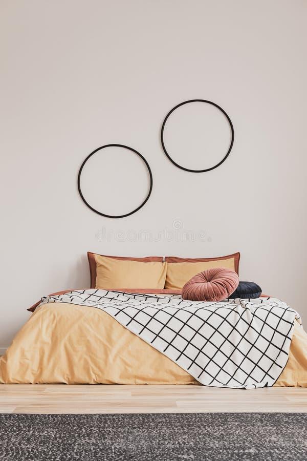 Vertikale Ansicht des eleganten Schlafzimmerinnenraums mit Königgrößenbett mit Gelb und Ingwerbettwäsche und der runden Rahmen au lizenzfreies stockbild