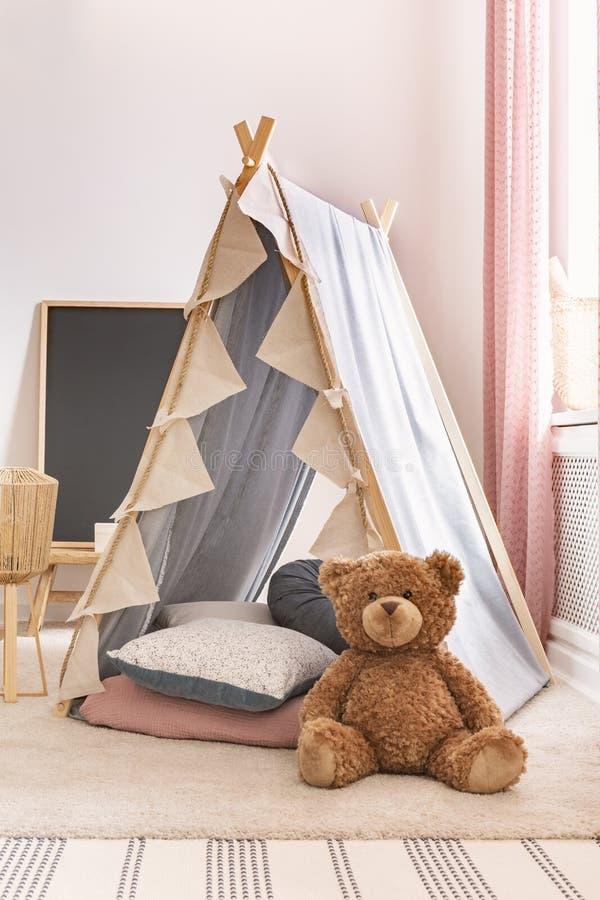 Vertikale Ansicht des Teddybären nahe bei Zelt mit Kissen im Spielzimmer des nettes Kindes, wirkliches Foto stockbild