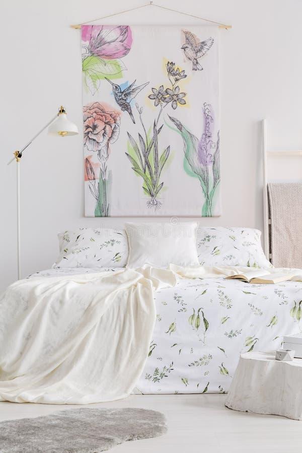 Vertikale Ansicht eines skandinavischen Artschlafzimmerinnenraums mit einem Bett kleidete im weißen Leinen mit gemalten Grünpflan lizenzfreie stockfotografie