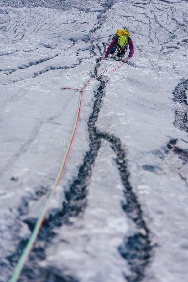 Vertikale Aufnahme einer Person, die in den Alpen in Österreich auf einen Felsen klettert - Konzept der Herausforderungen überwin lizenzfreie stockfotos