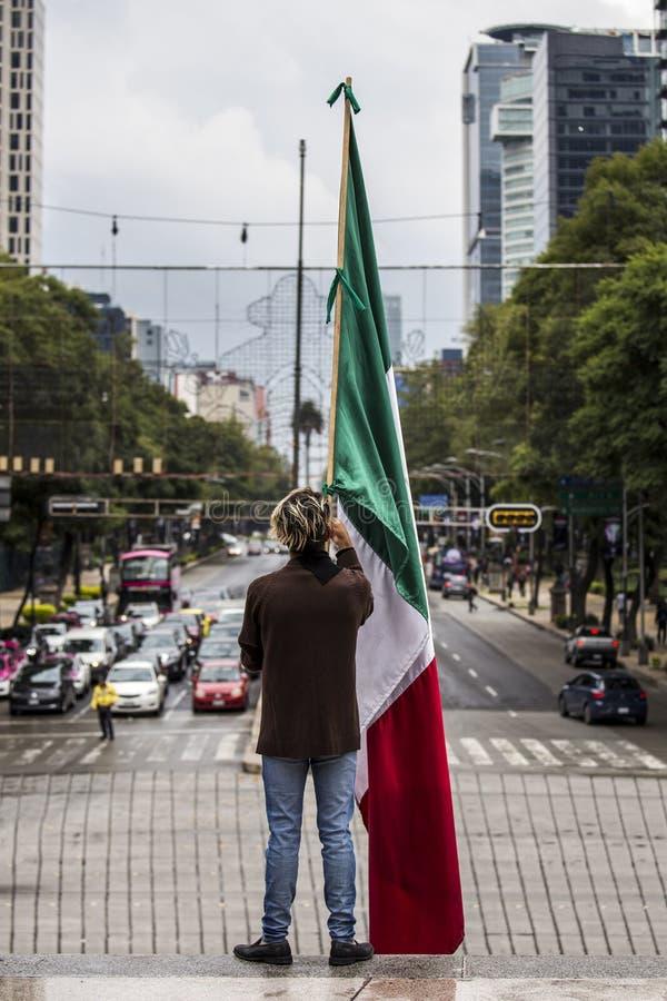 Vertikale Aufnahme einer Person, die eine Flagge in der Mitte der Straße patriotisch hält stockfoto