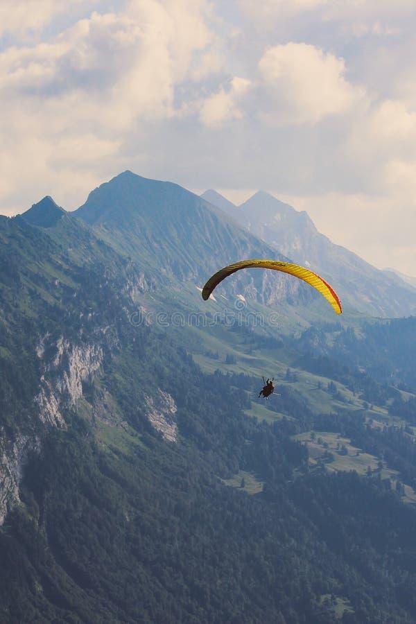 Vertikale Fotografie von Tandemgleitschirmfliegen in Interlaken, die Schweiz im schlechten Wetter Fliegen über Schweizer Alpen im lizenzfreie stockbilder
