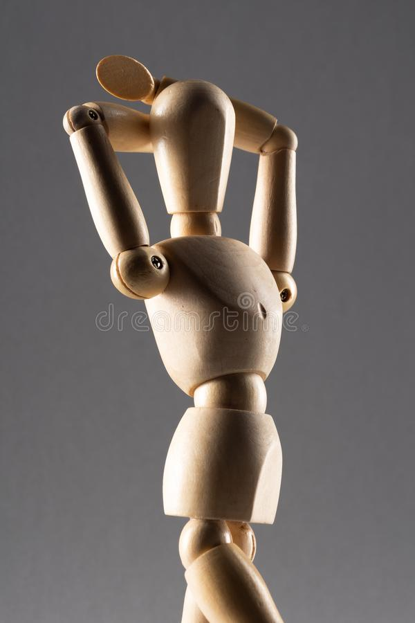 Vertikale Nahaufnahme einer hölzernen Posenpuppe mit beiden Händen hinter ihrem Kopf im Schatten lizenzfreie stockfotografie