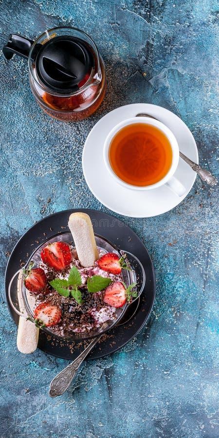 Vertikale Nahrungsmittelfahne Klumpennachtisch Fruchttee, frische Erdbeeren, tadellose Bl?tter und Zuckerpl?tzchen stockfotografie