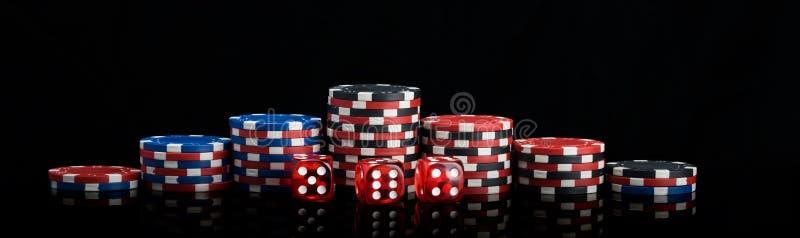 Vertikale Reihen des Hintergrundes von verschiedenen Pokerchips und von rotem Würfelstand auf einem langen Foto des schwarzen Hin stockbild