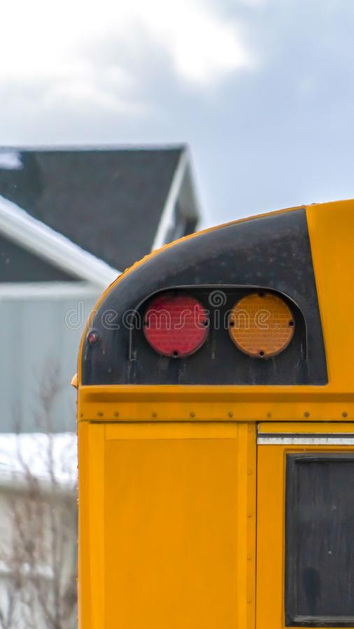 Vertikaler Abschluss oben der Rückseite eines Schulbusses mit einem Fenster und einigen Signallichtern stockfotografie