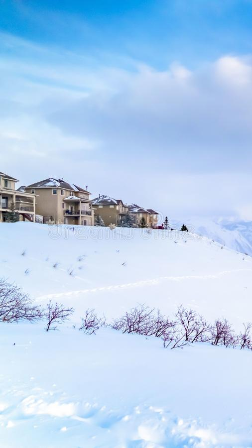 Vertikaler Panoramablick eines erstaunlichen schneebedeckten Berges gegen vibrierenden Himmel mit Wolken lizenzfreie stockfotos