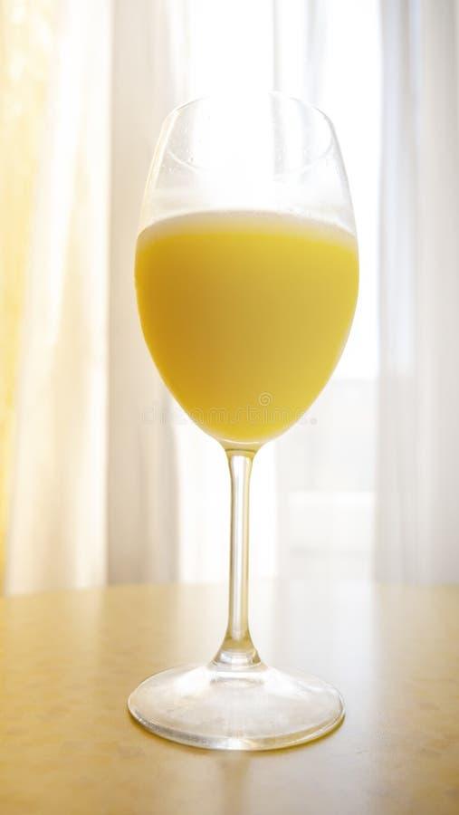Vertikaler Schuss der Nahaufnahme des frisch zusammengedrückten Orangensaftes in einem hohen Glas stockfotografie