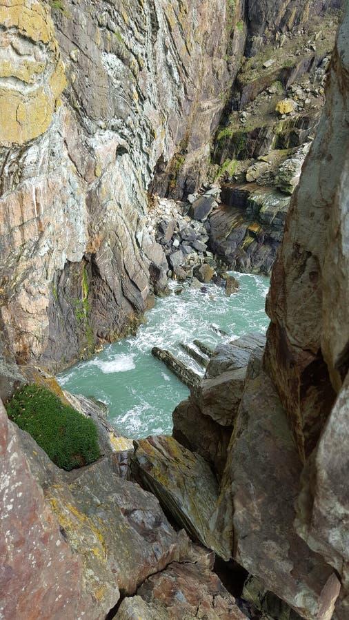 Vertikaler Schuss des Meerwassers, der Klippe und der Seeflora stockbild