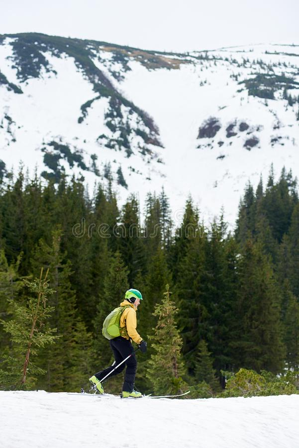 Vertikaler Schuss schneebedeckter Berg- und Off-Piste-Skifahrer Seitenansicht des männlichen Fußes allein auf Ski zu Fuß des Berg stockfotos