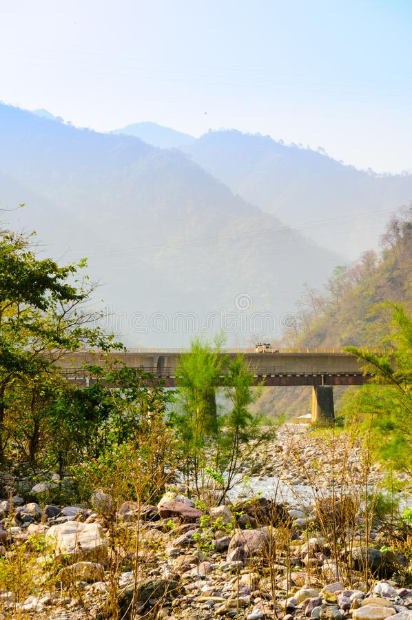 Vertikaler Schuss von Bergen, von Brücke und von trockenem Flussbett stockfotografie