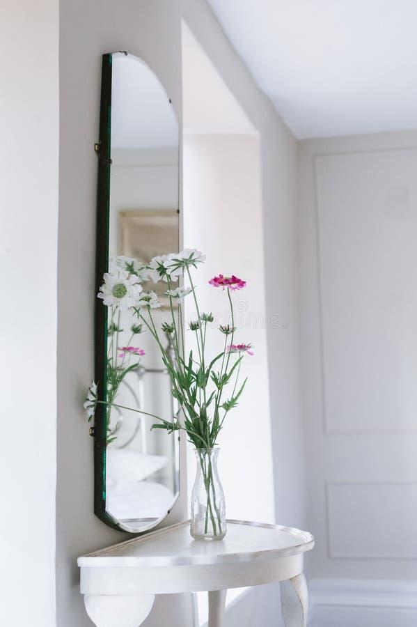Vertikaler Schuss von weißen und rosa Blumen in einem Glasflaschenvase vor einem Spiegel auf einem Glastisch lizenzfreie stockfotografie