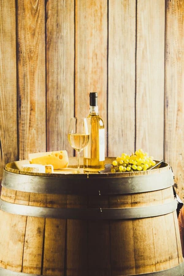Vertikaler Schuss von Weißwein in Glas, Flasche, Traube und Käse auf der Holzwand lizenzfreie stockfotos