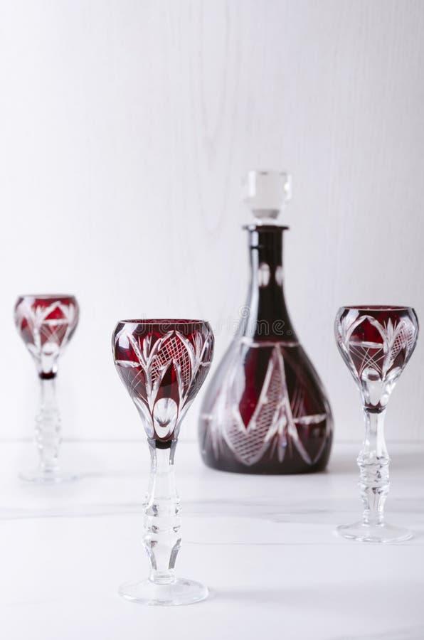 Vertikaler Schuss von Weinleseglaswaren, -gläsern und -dekantiergefäß auf der weißen Oberfläche stockfoto