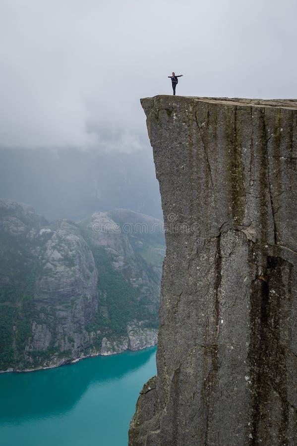Vertikaler Tourist des Fotos 0f, der an Prekestolen-rock& x27 steht; s-Rand stockfotografie
