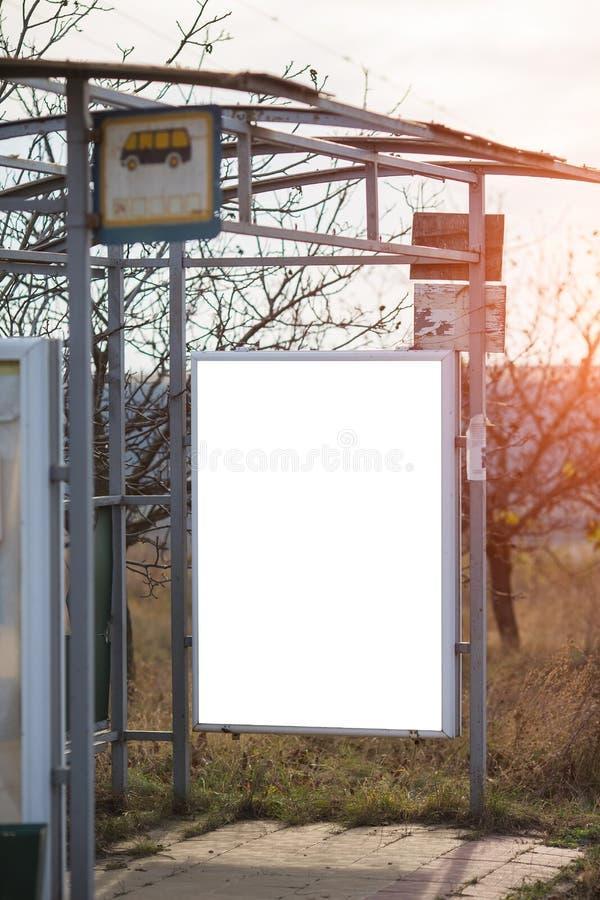 Vertikales Anschlagtafelmodell auf Bushaltestelle im Dorf lizenzfreie stockbilder