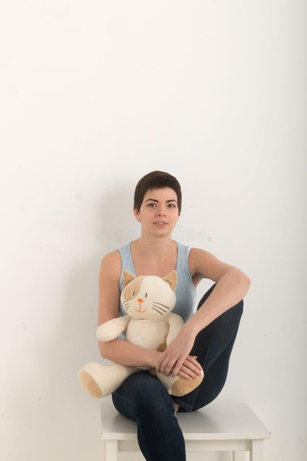 Vertikales Bild des jungen Mädchens Kamera, Porträt betrachtend einer schönen Brunettefrau mit einer reizenden Plüschspielzeugkat lizenzfreie stockbilder