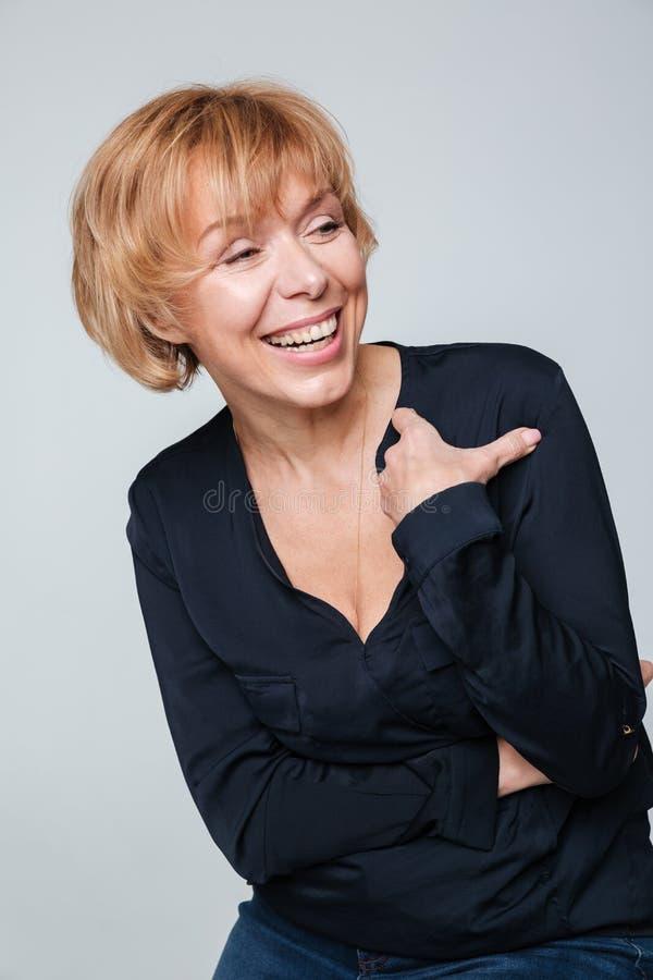 Vertikales Bild des Lachens der älteren Frau, die im Studio aufwirft stockfotos