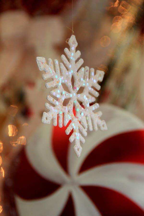 Vertikales Bild des Weihnachtsfensters mit roter und weißer Dekoration der Schneeflockenverzierung und -pfefferminz stockbilder