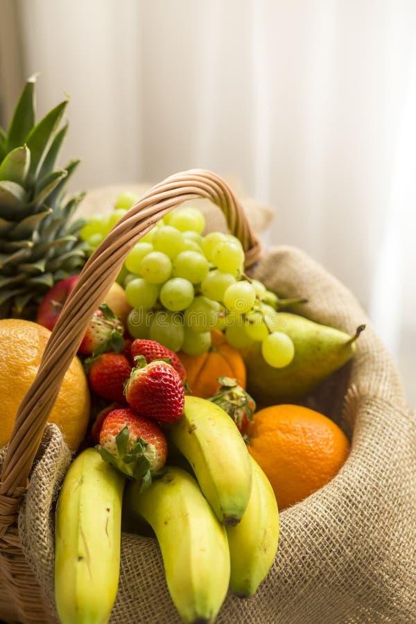 Vertikales Detail eines Korbes voll der Früchte auf einem hellen Hintergrund - hoher Schlüssel lizenzfreies stockbild
