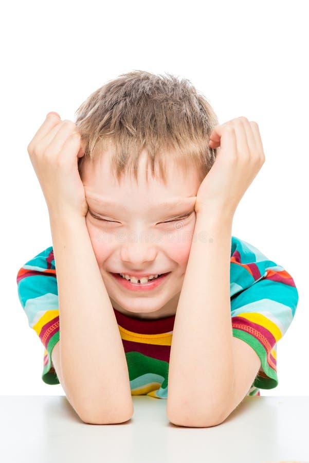 Vertikales emotionales Porträt eines Jungen von 10 Jahren am Tisch auf einem weißen Hintergrund lizenzfreie stockfotos