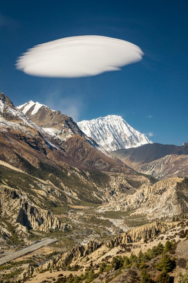 Vertikales Foto von Manang-Tal, von Tilicho-Spitze und von sonderbarer Wolke oben, Himalaja stockfotografie