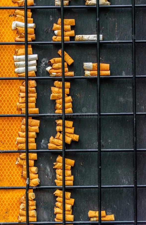 Vertikales Foto von Zigarettenkippen und von Eisennetz lizenzfreie stockfotos