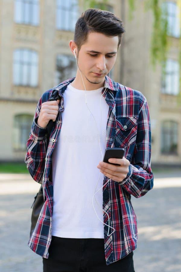 Vertikales Fotoporträt des hübschen attraktiven starken intelligenten Kerls, der im Internet neues Video unter Verwendung des Ger stockbild