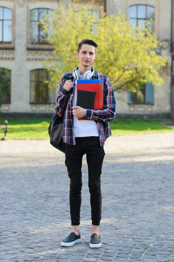 Vertikales Körpergrößenfoto in voller Länge des freundlichen Studenten der netten überzeugten Art, der vor Campus im Ausland steh lizenzfreie stockfotografie