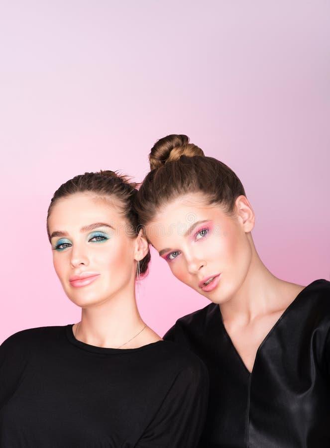 Vertikales Modeporträt mit freiem Raum Zwei junge Schönheiten im Schwarzen lizenzfreie stockbilder