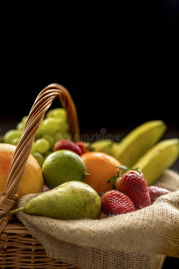 Vertikales Nahaufnahmedetail über einen Korb voll der Frucht auf einem dunklen Hintergrund stockbilder