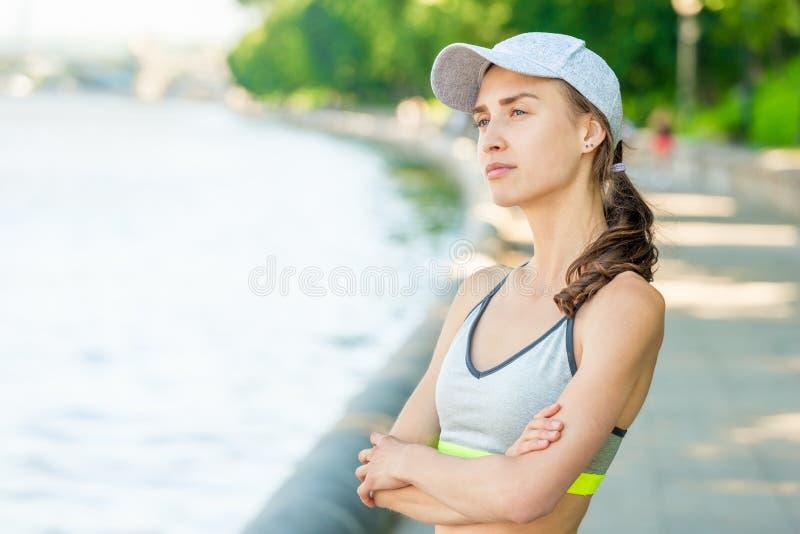 Vertikales Nahaufnahmeporträt einer träumerischen Sportlerin, die aufwirft stockfotos