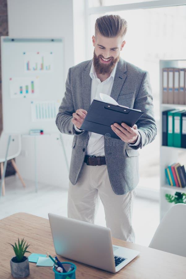 Vertikales Porträt des erfüllten glücklichen jungen Unternehmerschauens stockfotografie