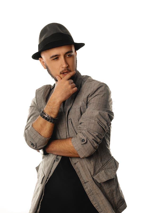 Vertikales Porträt des jungen Mannes des Zaubers beim Hut- und Jackenschauen stockfotos