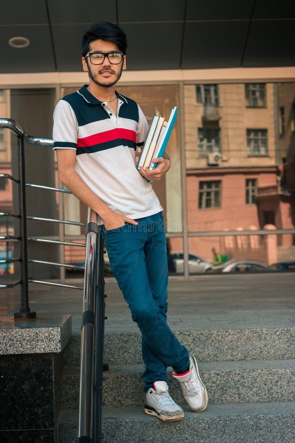 Vertikales Porträt des netten Studentenjungen in den Gläsern stockfoto